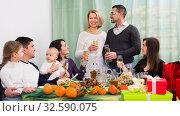 Купить «Positive family sitting at holiday table», фото № 32590075, снято 6 апреля 2020 г. (c) Яков Филимонов / Фотобанк Лори