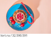 Christmas holiday cookies homemade sweet dessert on a blue plate and attributes symbols of the New Year top view on a peach color background with copy space. Стоковое фото, фотограф Светлана Евграфова / Фотобанк Лори