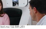 Купить «Ophthalmology treatment - a young smiling woman checking her visual acuity with a special big optometry machine then talking about it with a doctor», видеоролик № 32591251, снято 24 февраля 2020 г. (c) Константин Шишкин / Фотобанк Лори