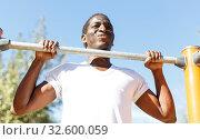 Купить «Active african american man doing workout at pull-up bar in park», фото № 32600059, снято 3 ноября 2018 г. (c) Яков Филимонов / Фотобанк Лори