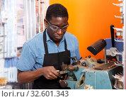 Professional skilled key cutter making duplicates of door keys. Стоковое фото, фотограф Яков Филимонов / Фотобанк Лори