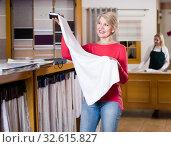 Купить «Mature woman choosing interesting fabric», фото № 32615827, снято 15 февраля 2017 г. (c) Яков Филимонов / Фотобанк Лори
