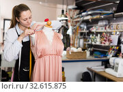Купить «Female seamstress is thinking about new dress for collection of clothes near mannequin», фото № 32615875, снято 5 мая 2018 г. (c) Яков Филимонов / Фотобанк Лори