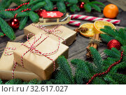 Christmas presents in retro wrapping, cinnamon and green dense fir branch. Стоковое фото, фотограф Константин Лабунский / Фотобанк Лори