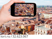 Travel concept - tourist photographs Verona cityscape in Italy from tower Torre dei Lamberti in spring on smartphone. Стоковое фото, фотограф Zoonar.com/Valery Voennyy / easy Fotostock / Фотобанк Лори
