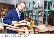 Confident young craftsman looking at book before start renovate antique chair. Стоковое фото, фотограф Яков Филимонов / Фотобанк Лори