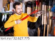 Купить «Male customer examining pitchforks», фото № 32627775, снято 2 марта 2017 г. (c) Яков Филимонов / Фотобанк Лори