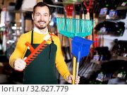 Купить «Seller displaying various items in garden equipment shop», фото № 32627779, снято 2 марта 2017 г. (c) Яков Филимонов / Фотобанк Лори