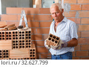 Man inspecting brick for installing wall. Стоковое фото, фотограф Яков Филимонов / Фотобанк Лори