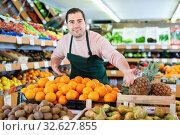 Купить «Young man in apron selling fresh oranges and fruits on the supermarket», фото № 32627855, снято 27 апреля 2019 г. (c) Яков Филимонов / Фотобанк Лори