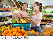 Купить «Cheerful family couple standing with full grocery cart after shopping», фото № 32627863, снято 27 апреля 2019 г. (c) Яков Филимонов / Фотобанк Лори