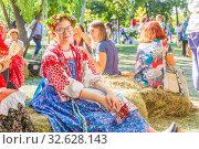 Купить «Russia Samara August 2019: Flower Festival. Girls in national Russian costumes are sitting on straw bundles.», фото № 32628143, снято 24 августа 2019 г. (c) Акиньшин Владимир / Фотобанк Лори