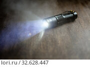 Купить «Tactical waterproof flashlight. LED flashlight shines on the table in smoke.», фото № 32628447, снято 11 декабря 2019 г. (c) Александр Якимов / Фотобанк Лори