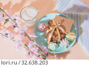 Fresh baked oat crispy cookies on a blue plate on a peach color background with mockup, milk, French multi-colored meringues. Delicious culinary sweet dessert, romantic festive breakfast, food, snacks. Стоковое фото, фотограф Светлана Евграфова / Фотобанк Лори
