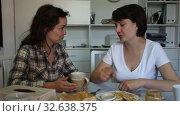Купить «Smiling young female friends gossiping on sofa in home interior», видеоролик № 32638375, снято 27 мая 2019 г. (c) Яков Филимонов / Фотобанк Лори