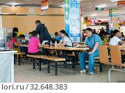 Купить «China, Heihe, July 2019: People dine at a cafe in the Huafu shopping center», фото № 32648383, снято 10 июля 2019 г. (c) Катерина Белякина / Фотобанк Лори
