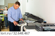 Купить «Worker is printing a file, document in the office room», фото № 32648467, снято 4 июня 2020 г. (c) Яков Филимонов / Фотобанк Лори