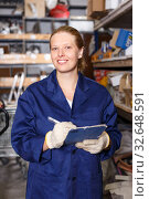 Купить «Young female worker holding notebook and looking construction materials at shelves», фото № 32648591, снято 20 сентября 2018 г. (c) Яков Филимонов / Фотобанк Лори