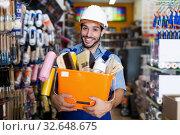 Купить «Positive guy painter holding basket with tools», фото № 32648675, снято 13 сентября 2017 г. (c) Яков Филимонов / Фотобанк Лори