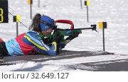 Junior biathlon competitions East Cup. Sportswoman biathlete aiming, rifle shooting, reloading prone position. Biathlete Kryukova Arina Kazakhstan in shooting range (2019 год). Редакционное видео, видеограф А. А. Пирагис / Фотобанк Лори