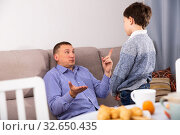 Upset father pointing to mistakes to his son while quarreling. Стоковое фото, фотограф Яков Филимонов / Фотобанк Лори