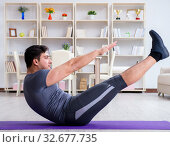 Купить «Young man exercising at home in sports and healthy lifestyle con», фото № 32677735, снято 3 мая 2017 г. (c) Elnur / Фотобанк Лори