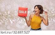 Купить «happy smiling young woman posing with sale sign», фото № 32697527, снято 30 сентября 2019 г. (c) Syda Productions / Фотобанк Лори