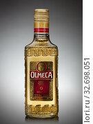 UKRAINE, KYIV-DECEMBER 12, 2012. Olmeca Tequila Cold bottle from Jalisco, Mexico on a gray background. Редакционное фото, фотограф Ярослав Данильченко / Фотобанк Лори