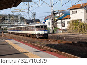 Electric train by West Japan Railway Company (JR West) comes to Miyajimaguchi Station. It is on Sanyo Main in Hatsukaichi, Hiroshima. Way to Miyajima island (2013 год). Редакционное фото, фотограф Кекяляйнен Андрей / Фотобанк Лори
