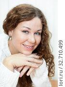 Curly hair woman portrait, looking at camera, dressed white pullover. Стоковое фото, фотограф Кекяляйнен Андрей / Фотобанк Лори