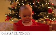 Купить «baby girl sitting in gift box over christmas tree», видеоролик № 32725035, снято 16 декабря 2019 г. (c) Syda Productions / Фотобанк Лори