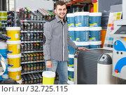 Купить «Happy customer standing near technical computer», фото № 32725115, снято 17 мая 2018 г. (c) Яков Филимонов / Фотобанк Лори