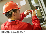 Electrician installing or repairing energy saving meter. Maintenance service. Стоковое фото, фотограф Дмитрий Калиновский / Фотобанк Лори