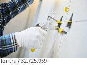Tiler installing large format tile on wall. tile leveling system. Стоковое фото, фотограф Дмитрий Калиновский / Фотобанк Лори