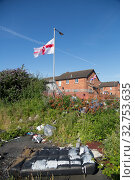 Great Britain, Northern Ireland, Belfast - Protestant part of West Belfast - neglected, burnt down square after the bonfire of Orangemens Day with Ulster flag (2019 год). Редакционное фото, агентство Caro Photoagency / Фотобанк Лори