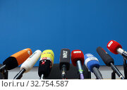 Berlin, Germany, microphones of different TV stations at a lectern (2018 год). Редакционное фото, агентство Caro Photoagency / Фотобанк Лори