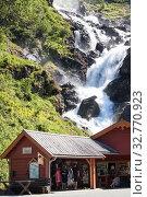 Local tourist center and souvenir shop is near Latefoss waterfall on Norwegian National Road 13. Latefossen fall consists of two separate streams flowing down. Odda, Hordaland, Norway (2018 год). Редакционное фото, фотограф Кекяляйнен Андрей / Фотобанк Лори