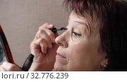 Mature woman doing makeup at home. Стоковое видео, видеограф Илья Шаматура / Фотобанк Лори