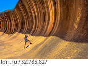 Купить «A sporty man enjoying surfing on the Wave Rock, a natural rock formation that is shaped like a tall breaking ocean wave, in Hyden, Western Australia. Happy funny male in Australian outback.», фото № 32785827, снято 8 мая 2020 г. (c) easy Fotostock / Фотобанк Лори