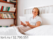 Elderly woman sitting comfortably on bed and using her digital tablet. Стоковое фото, фотограф Zoonar.com/Tomas Anderson / easy Fotostock / Фотобанк Лори