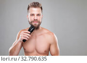 Handsome young bearded man trimming his beard with a trimmer. Стоковое фото, фотограф Zoonar.com/Tomas Anderson / easy Fotostock / Фотобанк Лори