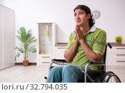 Купить «Young male invalid in wheel-chair suffering at home», фото № 32794035, снято 23 июля 2019 г. (c) Elnur / Фотобанк Лори