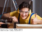 Купить «The worker working in repair workshop in woodworking concept», фото № 32795811, снято 11 августа 2017 г. (c) Elnur / Фотобанк Лори