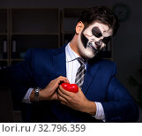 Купить «The businessman with scary face mask working late in office», фото № 32796359, снято 9 ноября 2017 г. (c) Elnur / Фотобанк Лори
