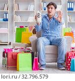 Купить «Young man after excessive shopping at home», фото № 32796579, снято 17 апреля 2017 г. (c) Elnur / Фотобанк Лори