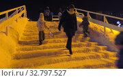 Купить «Дети катаются с ледяной горки на городской площади. Children ride on an ice slide in the town square.», видеоролик № 32797527, снято 23 декабря 2019 г. (c) Евгений Романов / Фотобанк Лори