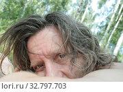 Пожилой мужчина с длинными волосами в березовой роще смотрит внимательно. Стоковое фото, фотограф Elizaveta Kharicheva / Фотобанк Лори