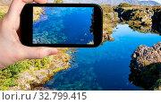 Купить «Travel concept - tourist photographs water in Silfra earth crack in rift valley of Thingvellir national park in Iceland in september on smartphone», фото № 32799415, снято 21 февраля 2020 г. (c) easy Fotostock / Фотобанк Лори