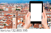 Travel concept - tourist photographs above view of Verona city with Torre del Gardello from tower Torre dei Lamberti in spring on tablet with cut out screen for advertising logo. Стоковое фото, фотограф Zoonar.com/Valery Voennyy / easy Fotostock / Фотобанк Лори