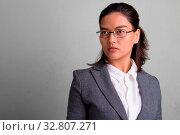 Купить «Studio shot of young beautiful Asian businesswoman wearing eyeglasses against white background», фото № 32807271, снято 27 мая 2020 г. (c) easy Fotostock / Фотобанк Лори